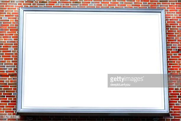large empty billboard on a red brick stone wall