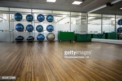 Large empty fitness studio with shelf of exercise balls : Stock Photo