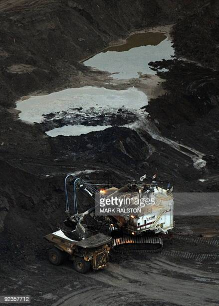A large excavator loads a truck with oil sands at the Shell Albian mine near the town of Fort McMurray in Alberta Province Canada on October 23 2009...
