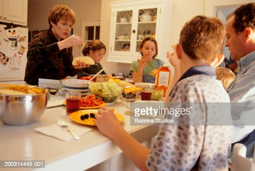 Large family at kitchen table eating tacos stock photo for Large family kitchen