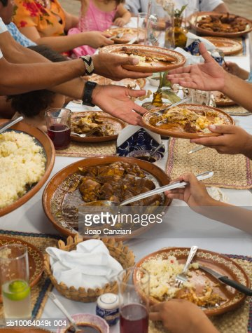 Large family dining outdoors, mid section : Foto stock