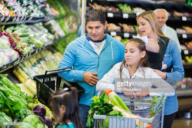 Large family shopping for healthy food together in supermarket