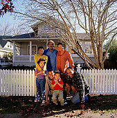 Large family standing at fence in front of house, portrait