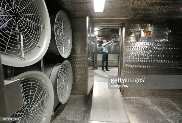 Large fans hang on a wall as chief of the Chemical Test Branch Adam Rogers checks out a wiring harness in a wind tunnel testing room at the small...