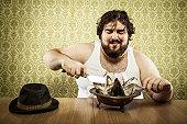Large fat man eating fish head soup at wood table