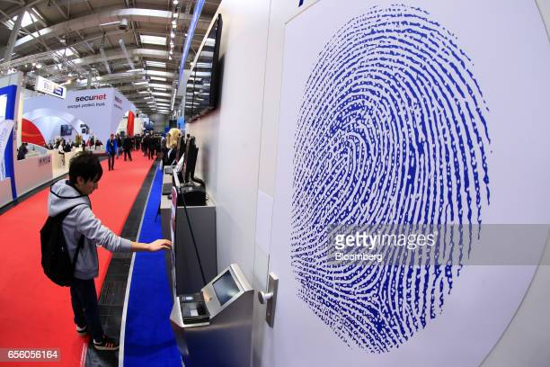 A large fingerprint motif sits on a display wall at the Dermalog Identification Systems GmbH pavilion at the CeBIT 2017 tech fair in Hannover Germany...