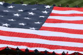 A large flag is unfurled in center field prior to the start of the game between the Florida Marlins and the New York Mets during their Opening Day...