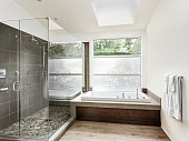 Master bath with tile floor, fancy cabinets, large mirror, and bathtub