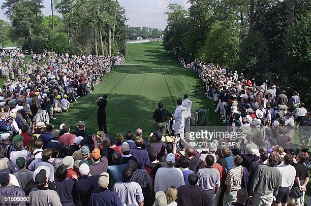A large gallery of fans line the tee box on the 18th hole as Tiger Woods of the US hits a drive 04 April 2001 during the final practice round for the...