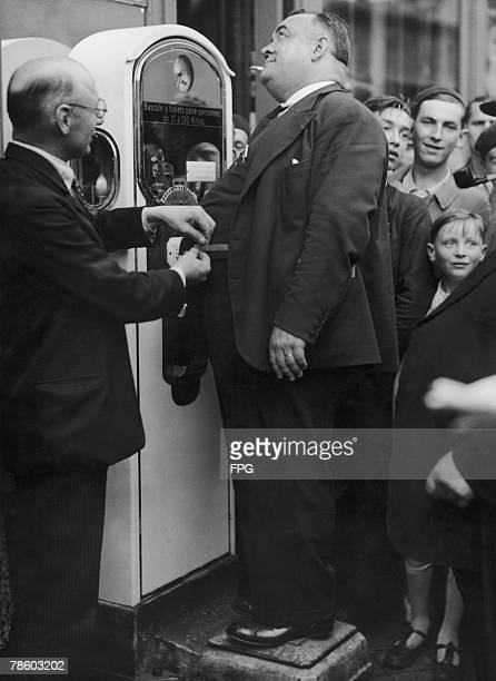 A large gentleman enters the competition for the largest waistline during the Rouen Gastronomic Fete 29th September 1934