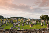 rural graveyard filled with old grave stones set on picturesque hill behind fieldstone wall