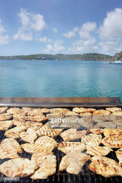 A large grill with a lot of cooking food in front of ocean.