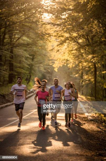 Large group of athletic people running a marathon through the forest.