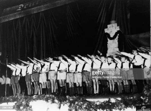 A large group of boys in uniforms consisting of shorts white shirts and ties give a Nazi salute on stage at a proNazi rally in Madison Square Garden...
