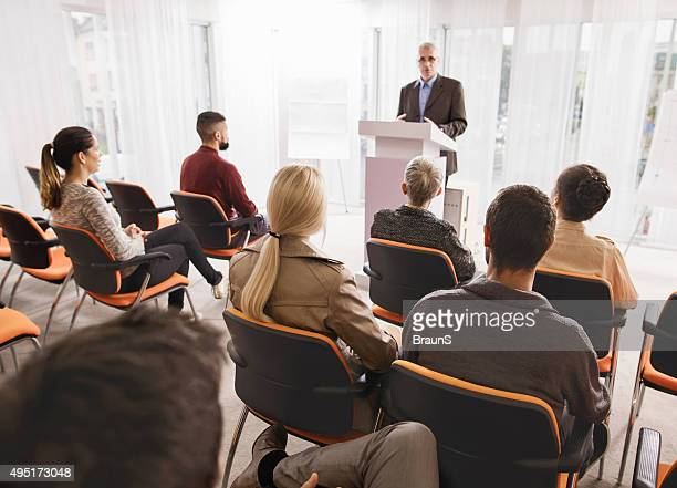 Large group of business people attending a seminar.