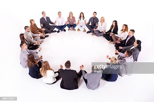 Large group of business people meditating.