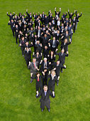 Large group of business people standing in triangle formation, cheering, elevated view