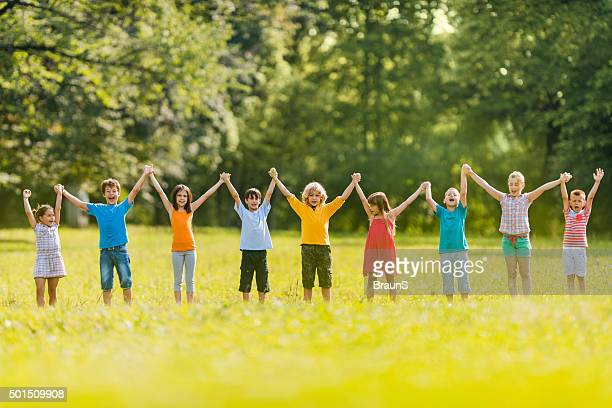 Large group of carefree children holding hands in the park.