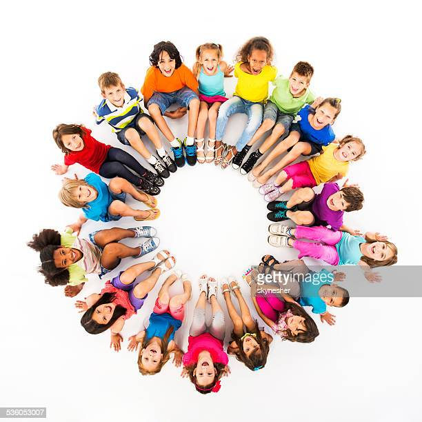 Large group of cheerful children sitting in a circle.