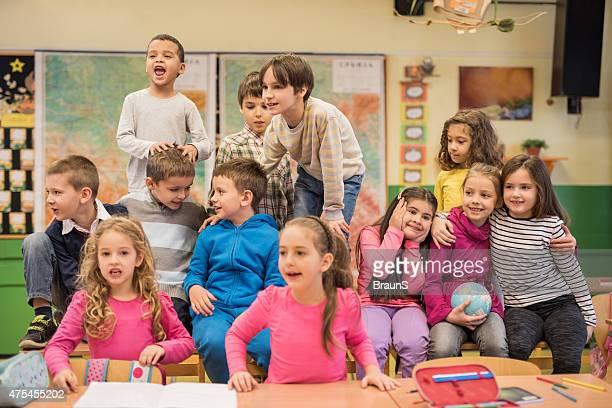 Große Gruppe von fröhlich elementare Schüler auf eine Pause.