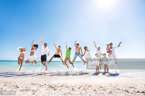 Large group of cheerful people jumping on the beach.