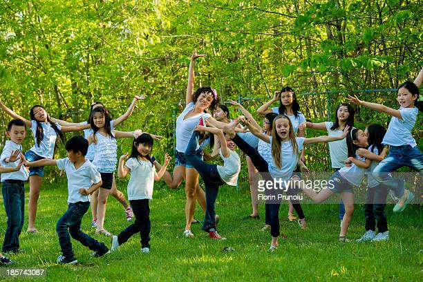Large group of children dancing in park