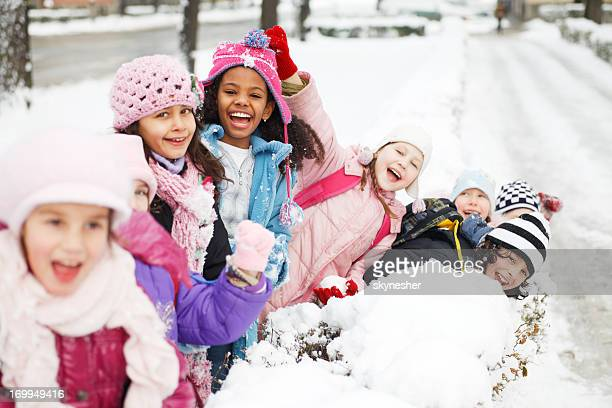 Large group of children having fun in the snow.
