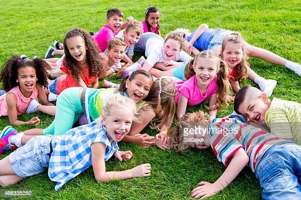 Große Gruppe von Kindern liegen auf dem Rasen