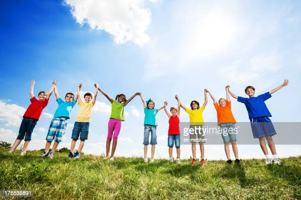 Large group of children with raised arms in nature.