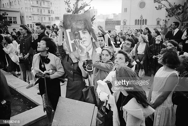A large group of fans several of whom hold up a poster wait to greet British pop group the Beatles who had just arrived to begin a US tour Los...