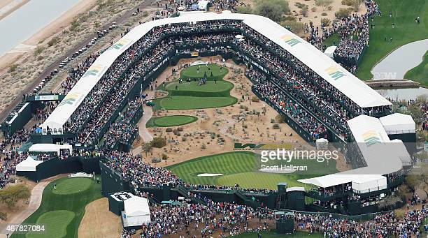 A large group of fans watch the play around the parthree 16th hole during the third round of the Waste Management Phoenix Open at TPC Scottsdale on...