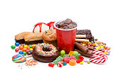 High angle view of a large group of multicolored products with high sugar level shot on white background. Food included in the composition are candies, donuts, chocolate bar, a glass of soda, ice crea