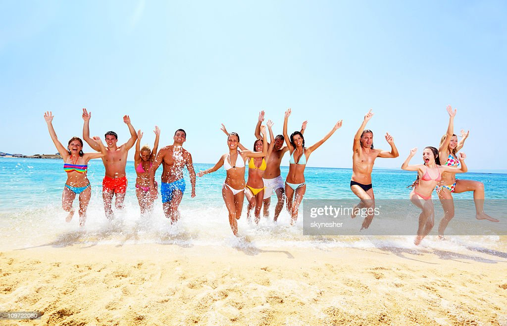 Large group of friends happy run from the sea. : Stock Photo
