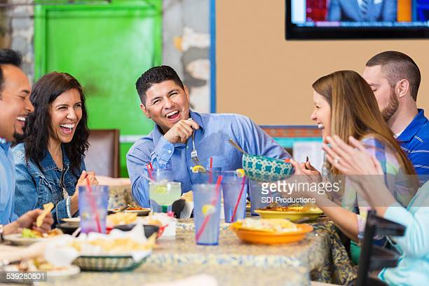 Large group of friends laughing during dinner in Tex-Mex restaurant