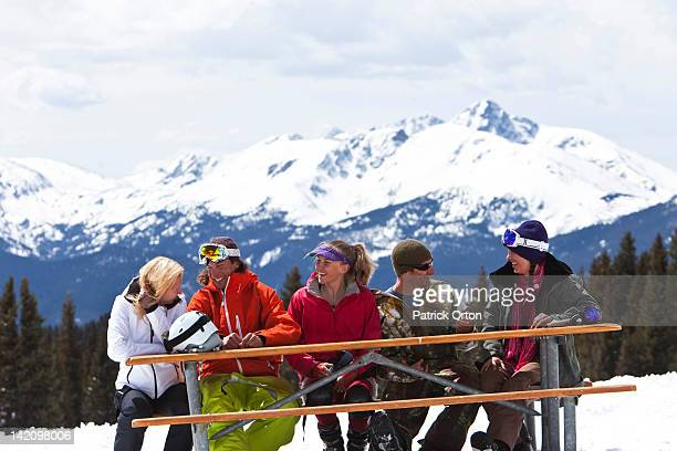 A large group of friends smile and laugh while enjoying a beautiful skiing day in Colorado.