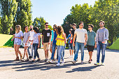 Large group of friends walking together at park. Multi ethnic group of people talking and walking on a sunny day. Friendship and lifestyle concepts