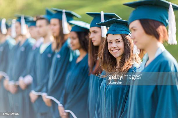 Large group of graduation students standing in a row outdoors.