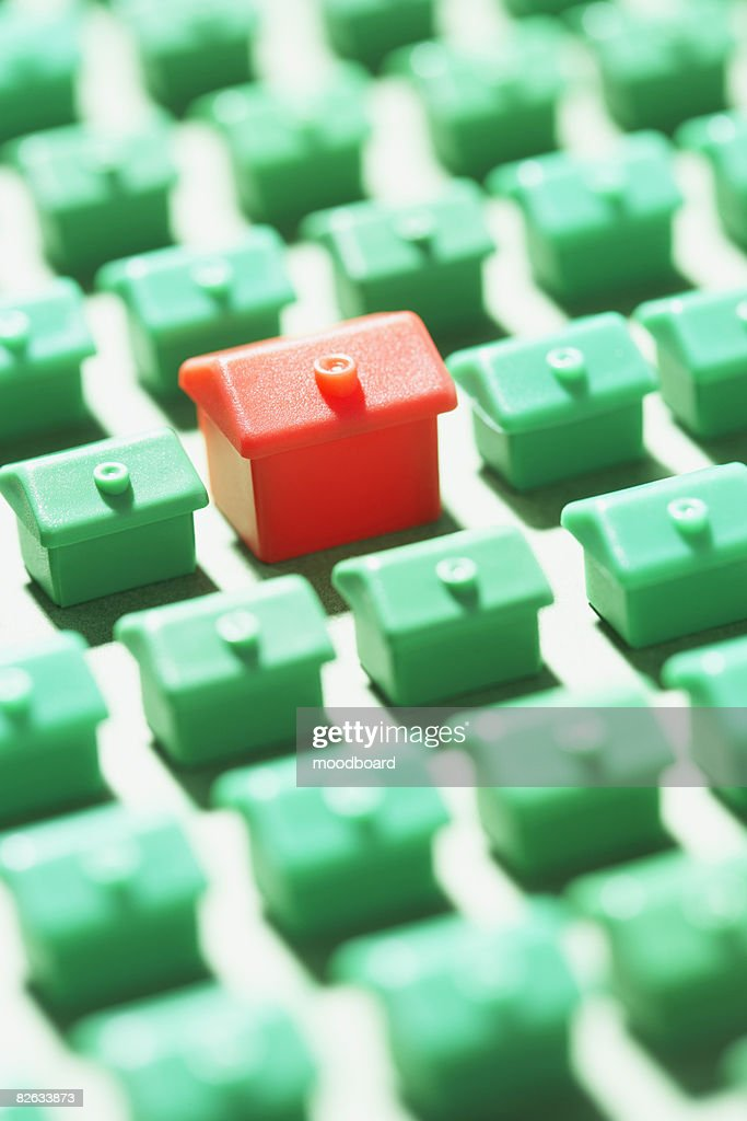 Large group of green model houses with one red in middle, close-up : Stock Photo