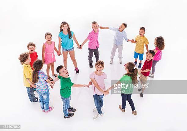 Grande gruppo di bambini felici che giocano Girotondo.