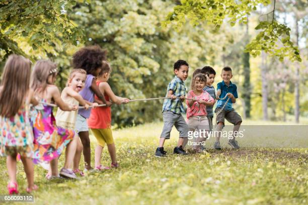 Large group of happy kids playing tug-of-war in nature.
