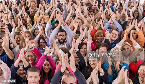 Große Gruppe von glücklichen Menschen applaudieren.