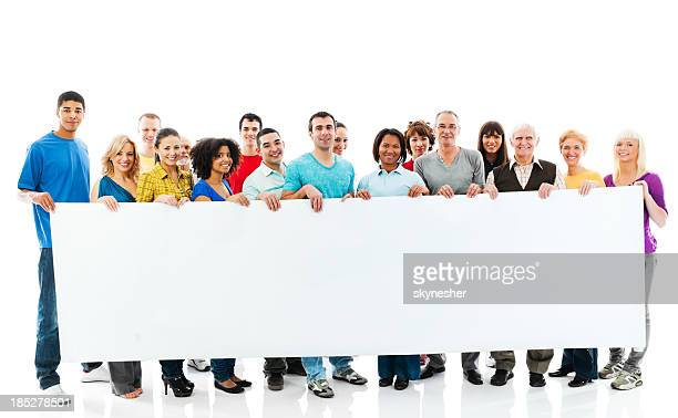 Large group of happy people holding a big white board.