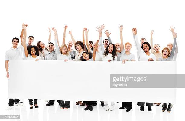Large group of happy people holding a white board.