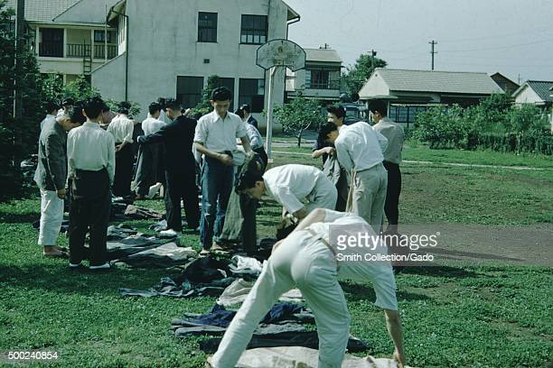 Large group of Japanese men in white shirts and black pants in the yard of a mission church sorting piles of clothing a basketball hoop in the...