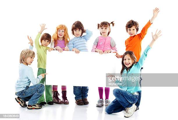 Large group of kids holding a big blank paper.