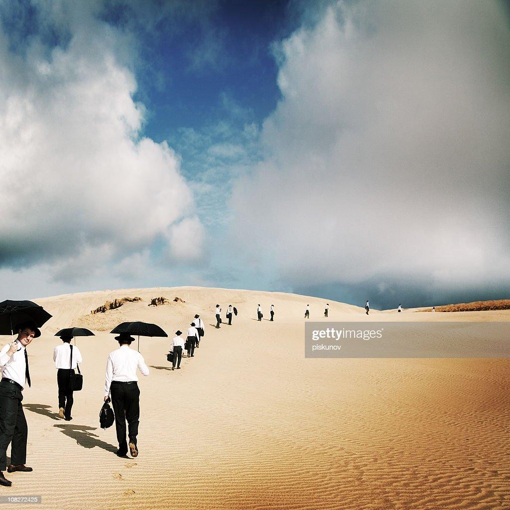 Large group of men travel in desert : Stock Photo