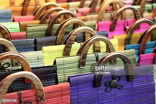 A large group of multi colored purses