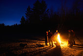 Large group of people around fire outdoors