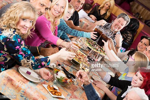 Large group of people celebrating at a pizza restaurant