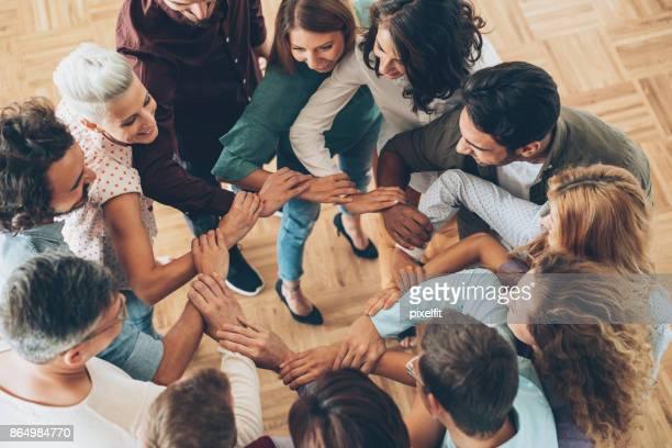 Large group of people connecting hands